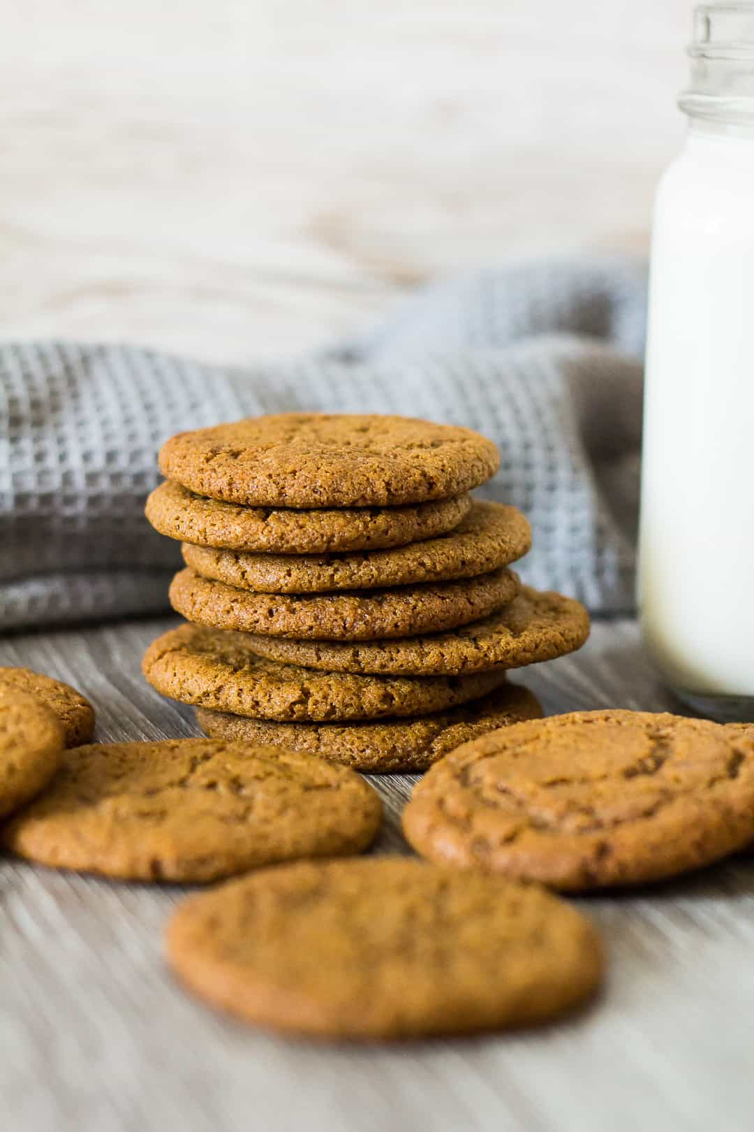A stack of Homemade Gingernut Cookies next to a glass of milk.
