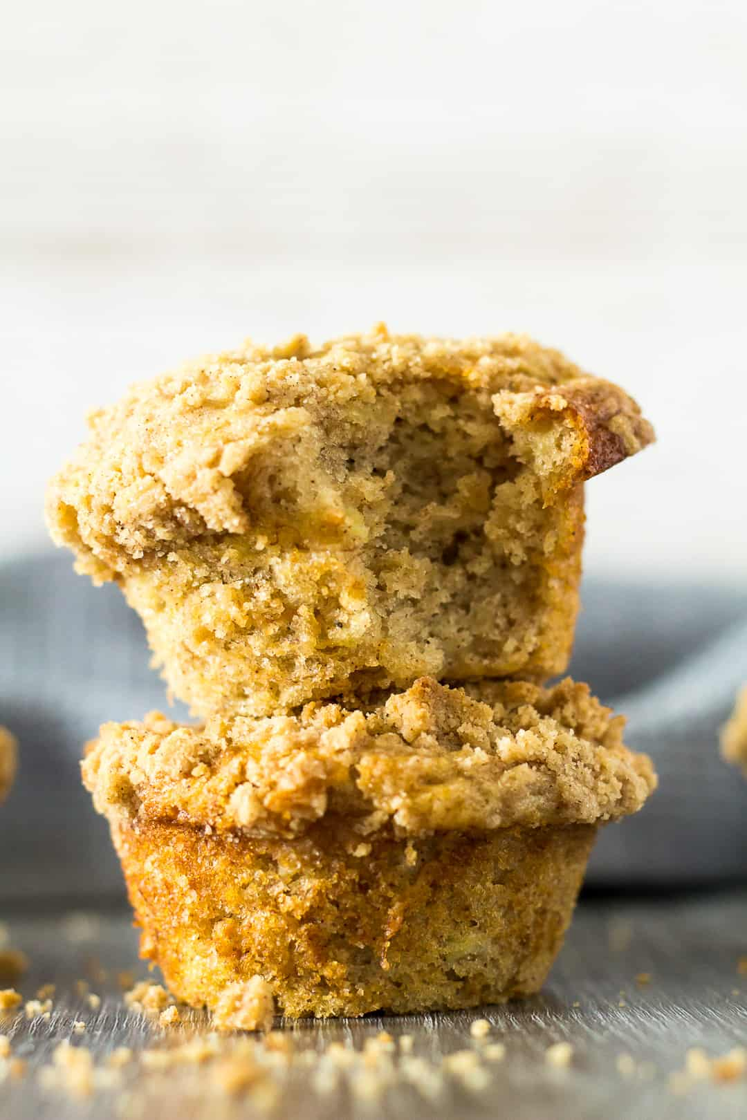 A stack of two Banana Crumb Muffins with a bite taken out of the top muffin.
