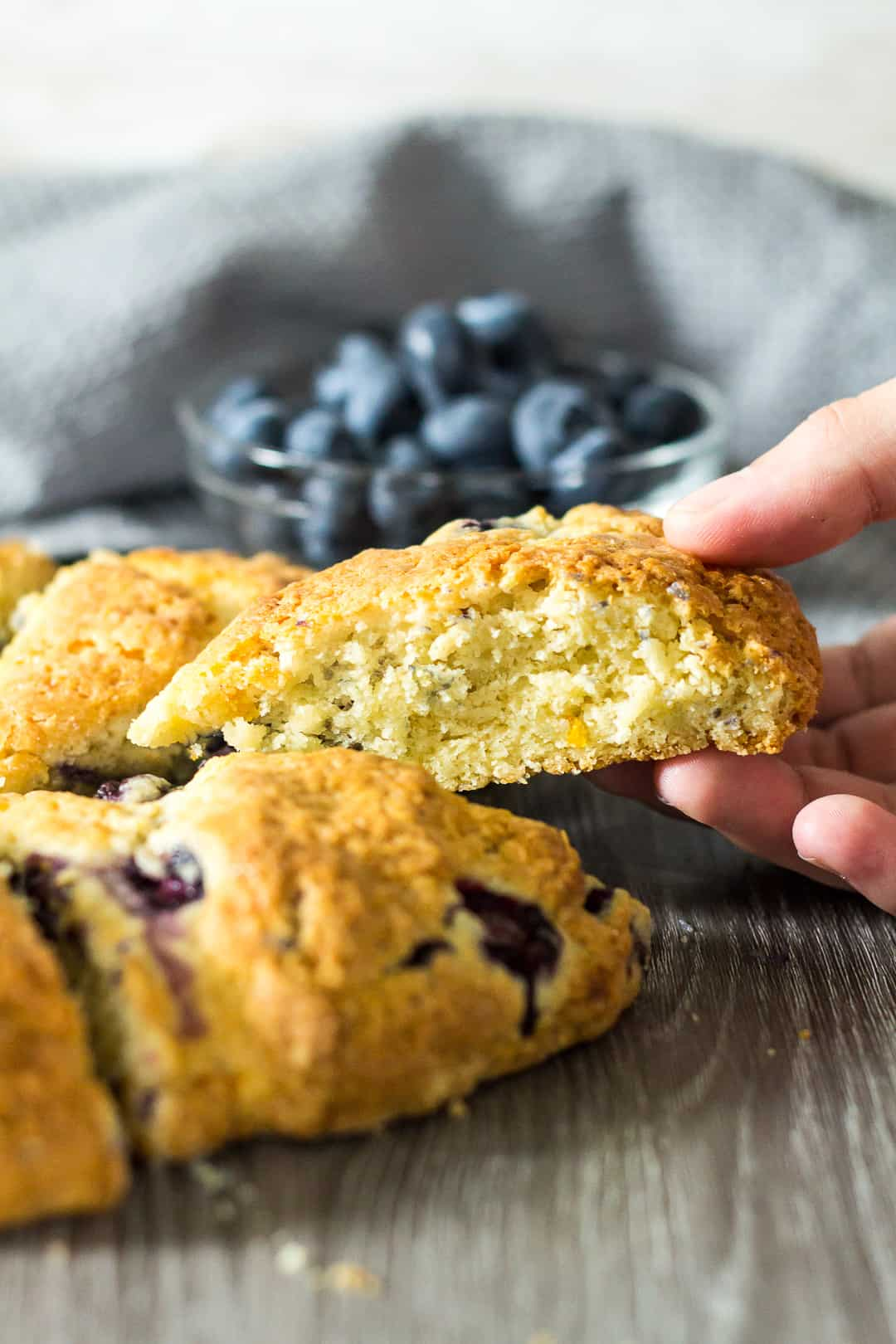 A Blueberry Orange Scone being picked up by hand from the batch of scones.