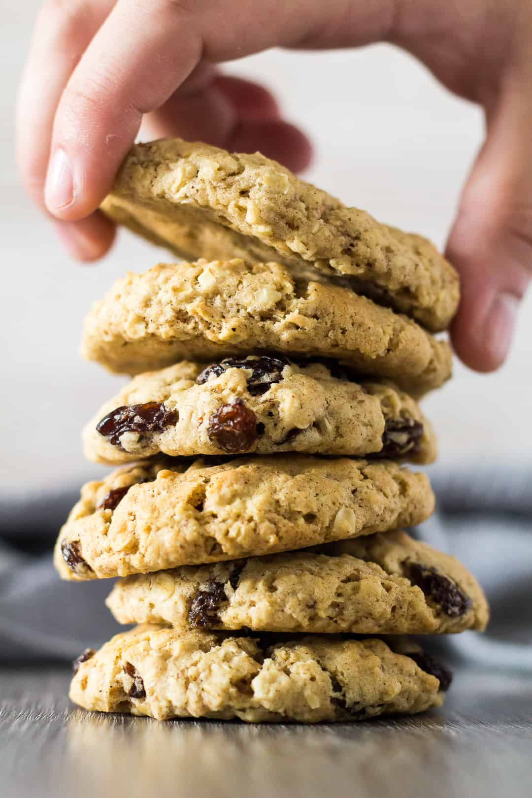 A stack of Oatmeal Raisin Cookies with the top cookie being picked up by hand.