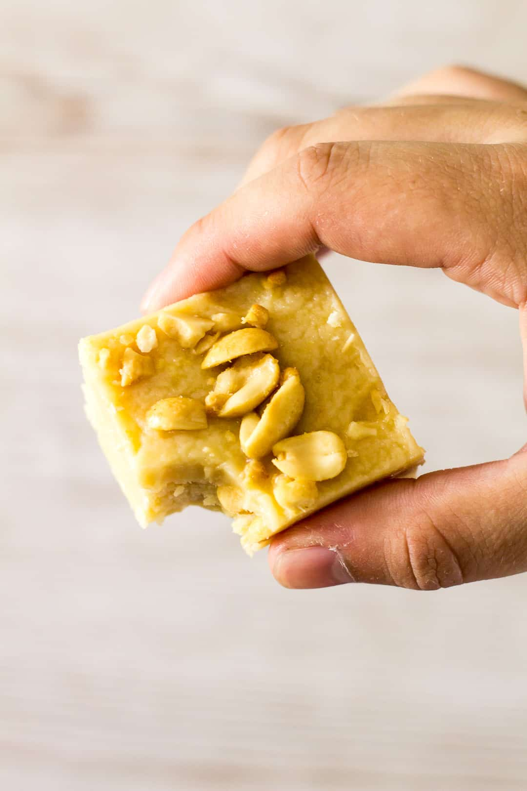 A bitten piece of Peanut Butter Fudge being held up by hand.