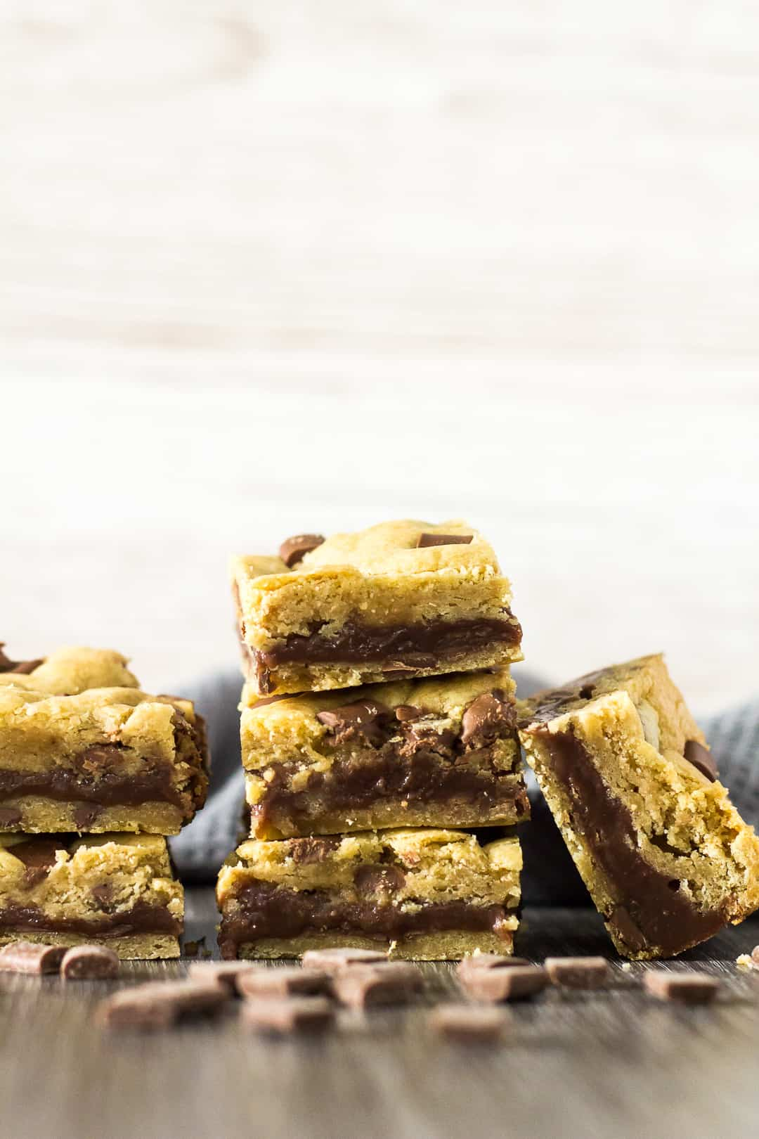 A sideview of Fudge Stuffed Chocolate Chip Cookie Bars stacked on top of each other.