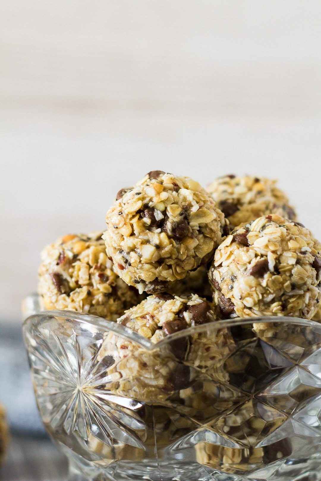A close-up of No-Bake Peanut Butter Coconut Energy Bites in a small glass bowl.