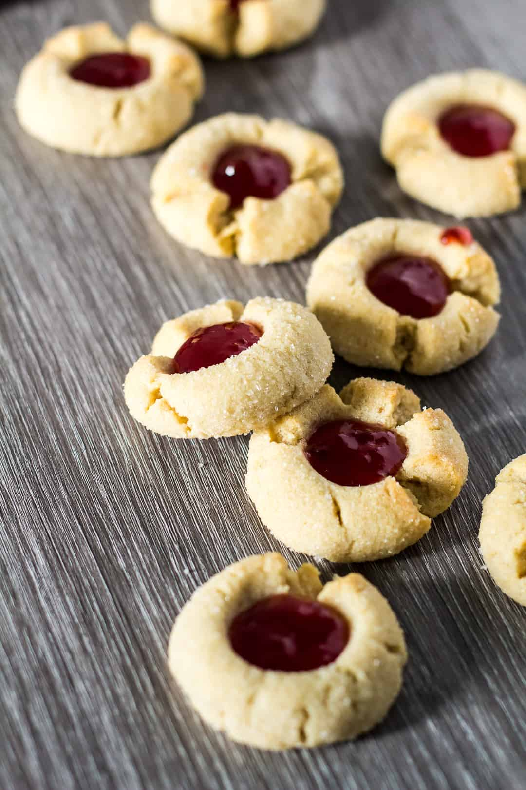 Peanut Butter & Jam Thumbprint Cookies scattered on a grey background.