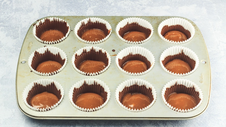 Muffin cases in a muffin pan filled with chocolate and caramel