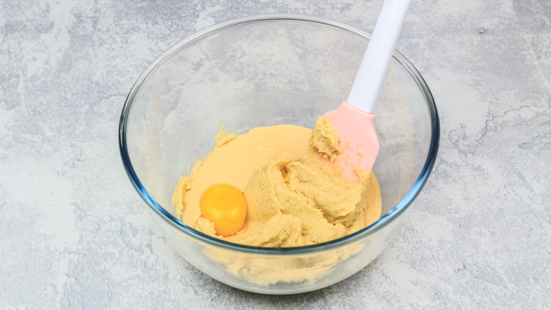 Adding egg yolk and eggnog to mixture in bowl.