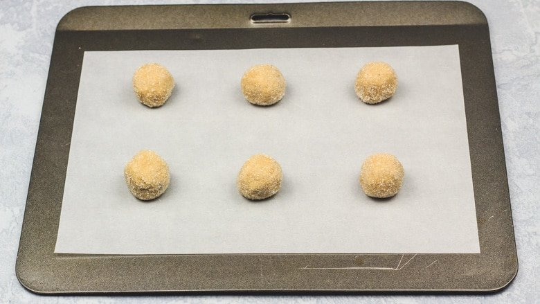 Cookie dough balls on baking tray.