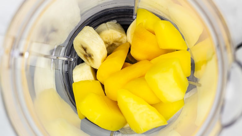 Banana slices and mango chunks in a blender.