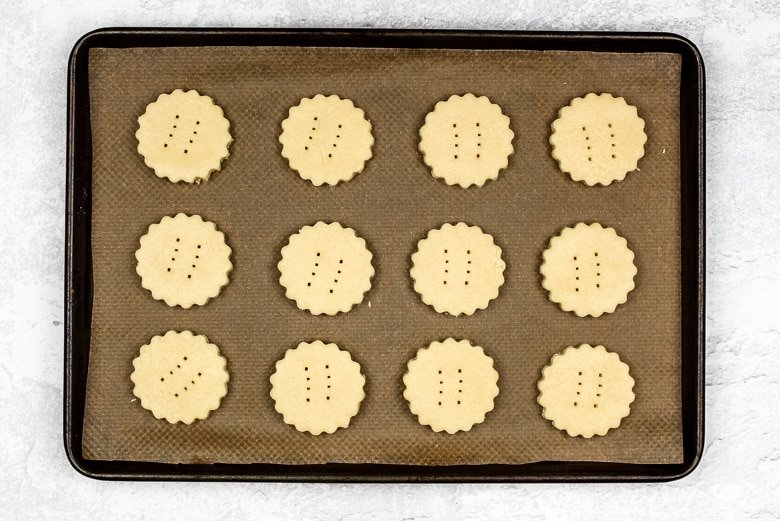 Cookie dough shapes on a lined baking tray ready to be baked.